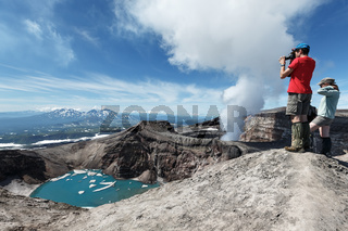 Tourists in crater of active Gorely Volcano takes a picture. Russia, Kamchatka Peninsula