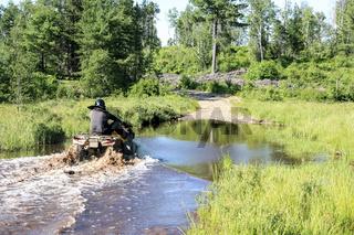 Man driving motocross ATV quad through splashing river lake water. Foy, Sudbury, Ontario, Canada.