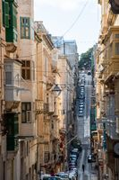Steep street in Valetta with tall buildings