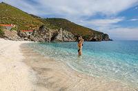 Young woman at the beach Kalamos in Evia island, Greece