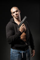 male gangster holding a gun isolated on dark