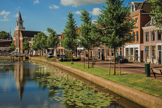 Canal with bascule bridge, church and brick houses at Weesp