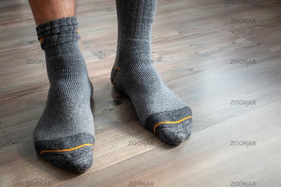 male feet in grey socks on a wooden floor