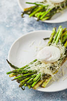 Green asparagus with poached egg and parmesan, vegetarian breakfast served on white plate on light background.
