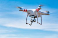 Flying quadcopter UAV with digital camera, takes aerial pictures world around from bird's eye view