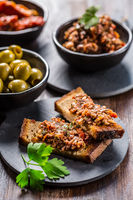 Crispy crostini with tapenade and ingredients. Tapenade - delicious olive paste from France.