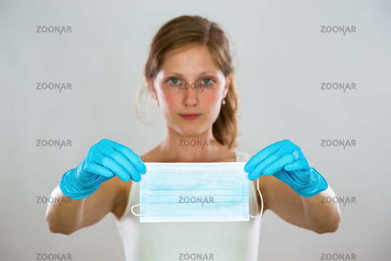 Young woman holding surgical face mask in blue rubber gloves in front of her