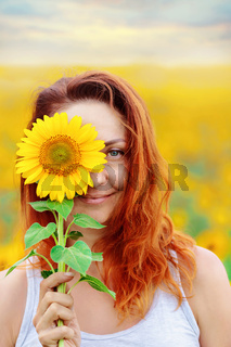Beautiful woman smiles and covers her face with a sunflower.