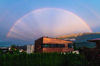Rainbow over modern copper building in Austrian alp mountains village during sunset, Tyrol, Austria