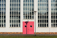 Two-leaf red door with the portholes and the street lamp