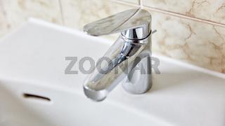 Wasserhahn am Waschbecken in einem Badezimmer