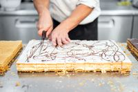 Close-up of a pastry chef cutting a large cake in portions at pastry shop.