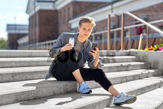 teenage boy with drink and smartphone in city