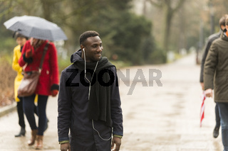 Young Man with Earphones on Park Road with Incidental People