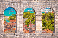 Trogir old city rooftops and turquoise archipelago view through stone windows