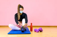 Fitness woman streching Relaxing after training and wearing protectve face mask during Covid 19