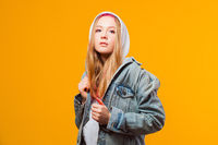 Cool young woman posing in jeans jacket on yellow background