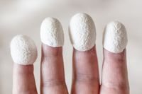 organic silk cocoons dressed on fingertips