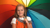 Charming little girl in orange dress holds rainbow colors umbrella standing and cheering in studio while looking at the camera