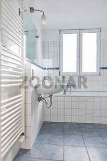 Modernes helles Bad mit Röhrenheizkörper und Badewanne