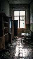 room with a window with a bed in an abandoned house in Chernobyl