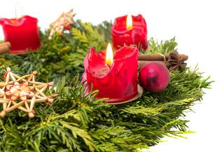 Verzierter Adventskranz aus Tannenzweigen mit brennenden roten Kerzen freigestellt auf weiß