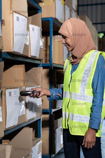Asian Islam Muslim warehouse worker do inventory