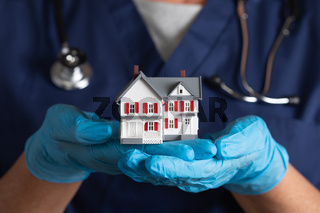 Female Doctor or Nurse Wearing Surgical Gloves Holding Model Home