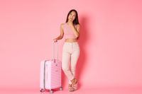 Travelling, holidays and vacation concept. Full-length of thoughtful attractive asian girl in summer clothes planning where to go, plan flight route, smiling pleased, standing with suitcase