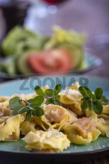 Tortellini mit Olivenöl auf einem blauen Teller