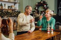 Happy elderly couple celebrating wedding anniversary. 60s happy retirement. Valentines seniors day. Champagne date