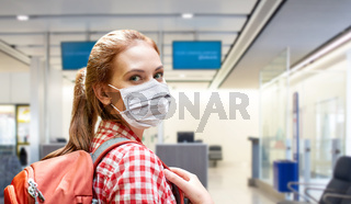 young woman in mask with backpack at airport