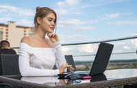 Beautiful young woman in white t-shirt is working on laptop and smiling while sitting outdoors in cafe. Young female using laptop for work. Female freelancer working on laptop in an outdoor cafe.