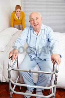 Senior am Bett zu Hause mit Gehhilfe
