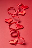Valentines day hearts and ribbon on red background.