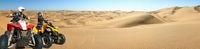 Quad ATV driving people. Happy smiling couple bikers in sand desert. Quad driving and skidmarks in panoramic sand dunes desert. Africa, Namibia, Namib, near Walvis Bay, Swakopmund.