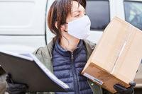 Lieferservice Paketbotin mit Mundschutz liefert Paket aus