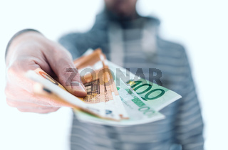 midsection of man holding banknotes in his hand handing it over to someone