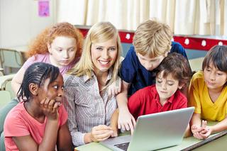 Kinder mit Lehrer im Informatikunterricht