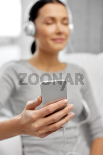 close up of woman with smartphone and headphones