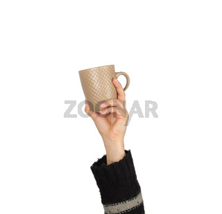 brown ceramic cup in a female hand on a white background