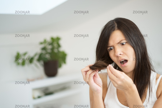 Woman checking the end of her hair for split ends