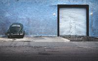 Dark green vintage Volkswagen beetle parking at abandoned blue building, Merida, Mexico