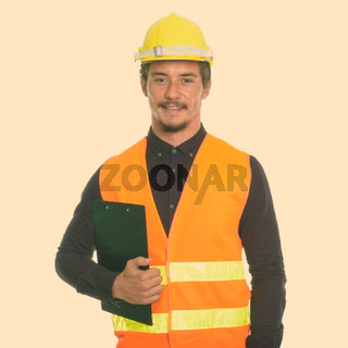 Studio shot of young happy man construction worker smiling while holding clipboard isolated against white background