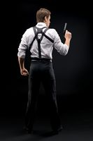 Style Muscular man with gun stand back to camera in dark