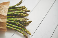 Fresh green asparagus in a brown paper bag. Healthy eating concept. Food for vegetarians