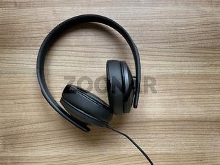 black around-ear headphones lying on wooden desk