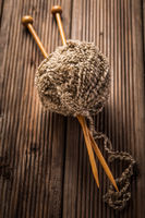 Ball of wool with knitting needles on wooden background. Concept of handcraft.