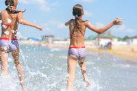 Spray soars after children run along the seashore