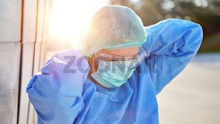 Mitarbeiter in Schutzkleidung während Coronavirus Pandemie legt Mundschutz an nach Pause